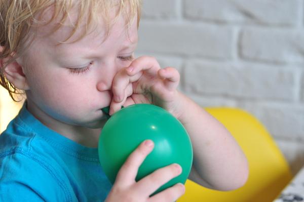 Ребенок надувает шарик